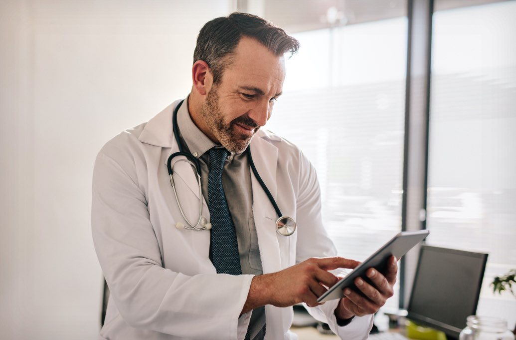 male doctor looking at tablet