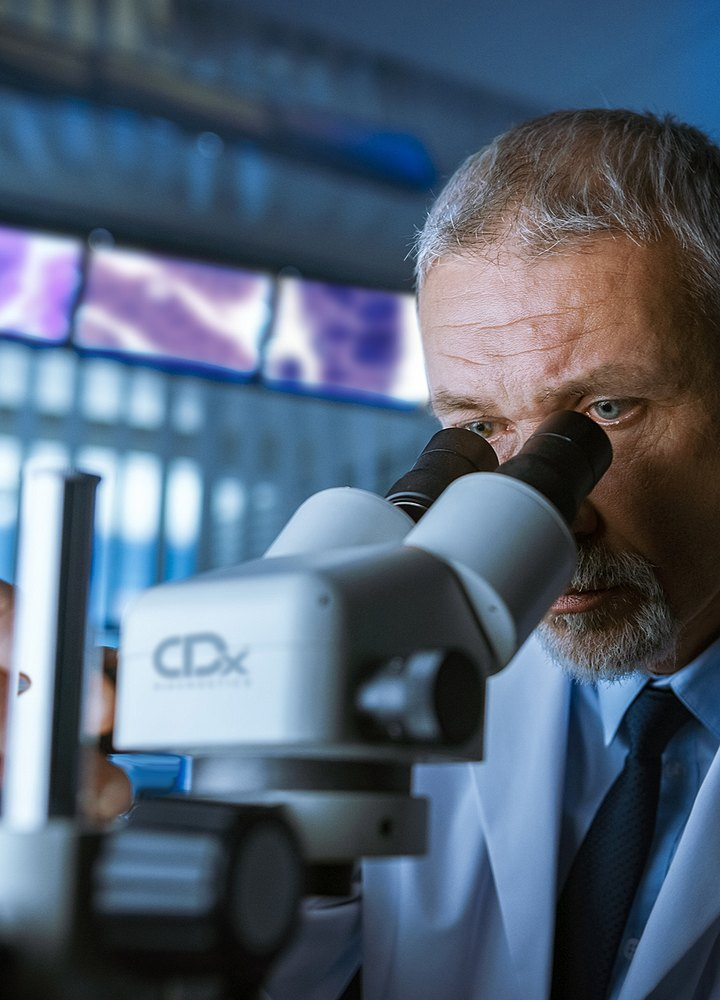 male doctor looking in microscope